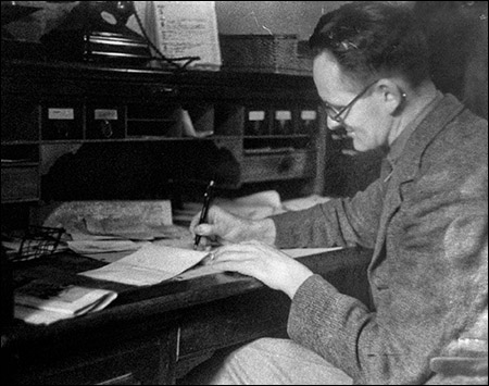 Photo of I B Griffith writing at his desk