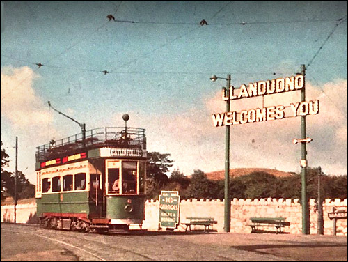 Old photo of tram passing welcome sign at Penrhyn Hill