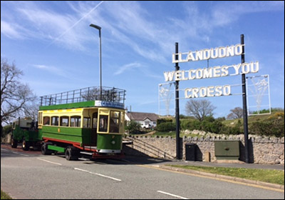 Photo of replica tram passing welcome sign at Penrhyn Hill